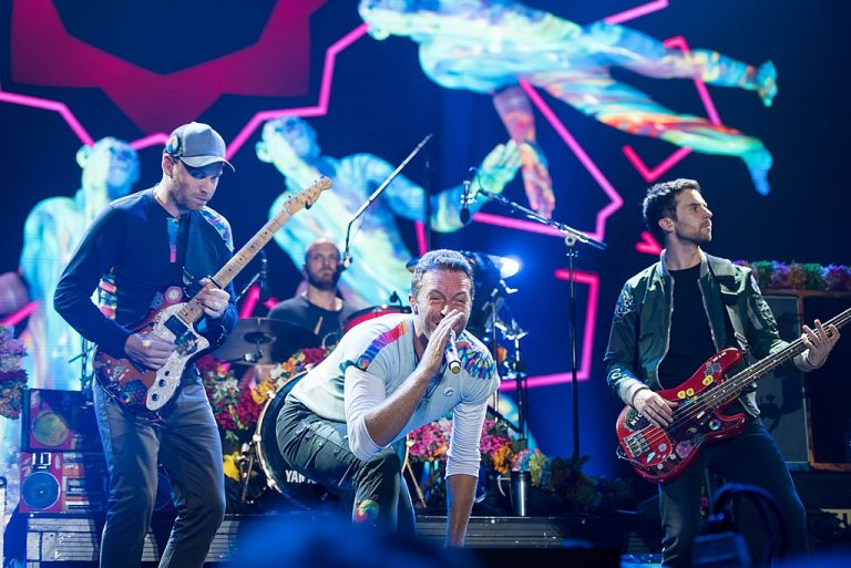 The band Coldplay performs onstage. Major record label organise concerts and world tours for bands and artists