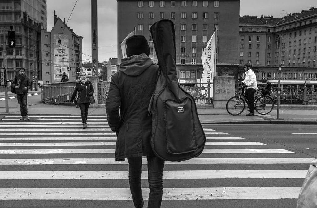 A man crosses the street with a guitar gig bag on his back.