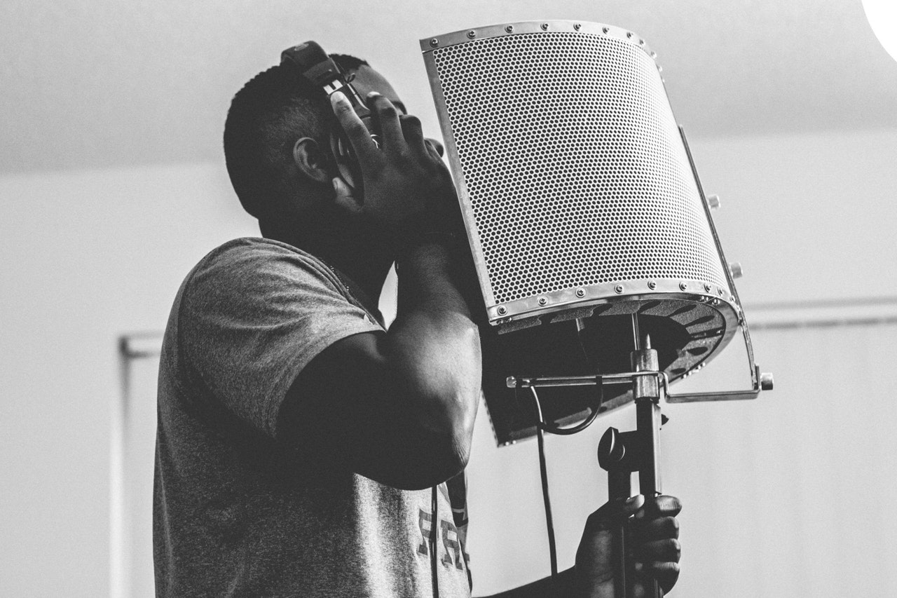 Man recording vocal tracks using a reflection filter on his microphone.