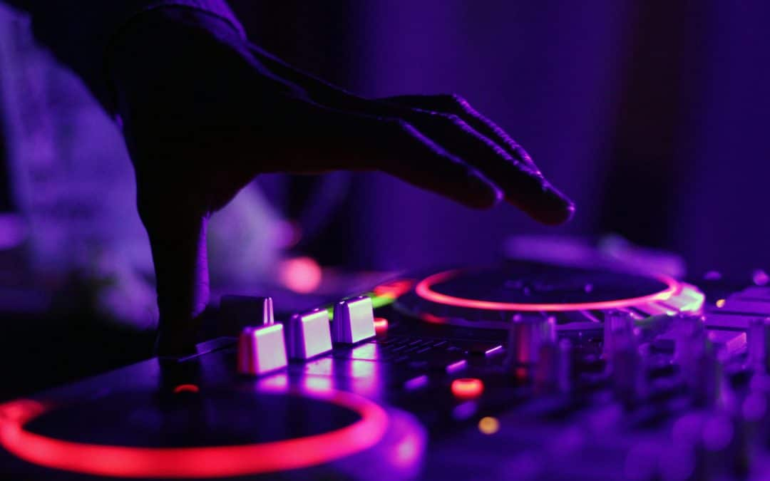 mixed in key: a DJ's hands are positioned over a lit mixing station in a dark club