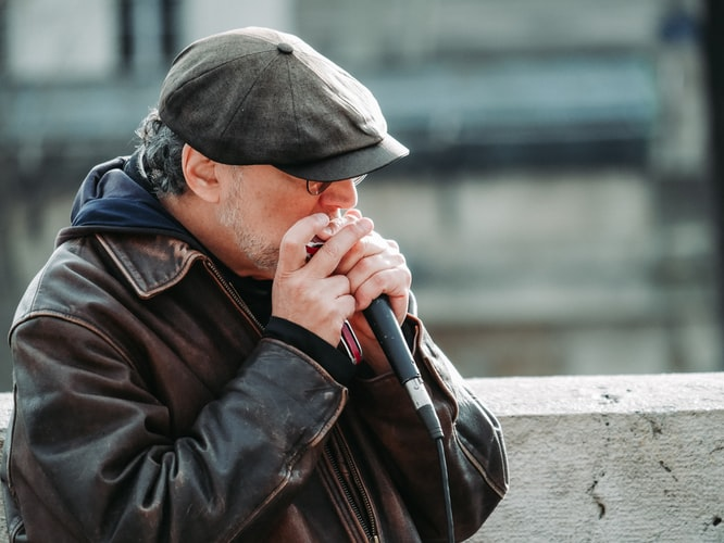 man in black jacket using harmonica